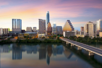 From the top floor of the Hyatt on Ladybird Lake, this Austin Skyline Picture was captured at sunset. Prominently displayed are the Austonian (the tallest building in Austin) and the iconic Frost Tower. In the foreground is Town Lake and Congress Bridge.